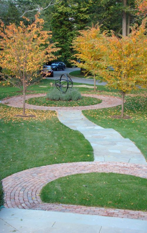 stone and brick walk with trees and garden sculpture in Hudson Valley garden