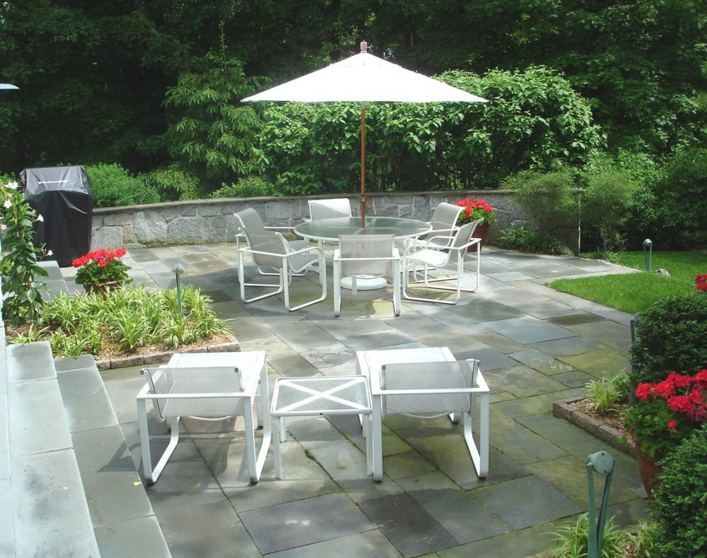 Slate patio design with stone wall